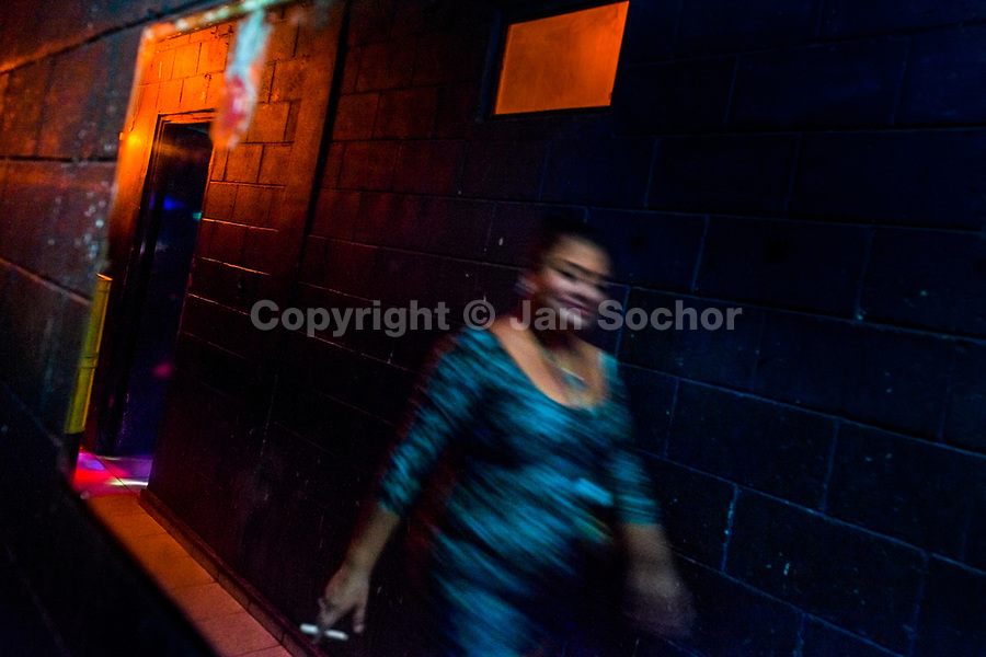 A Salvadoran sex worker walks in front of the mirror in the backstage of a sex club in San Salvador, El Salvador, 9 April 2018. Sex workers' task in the club is to be an entertaining and seductive companion. Performing erotic dance on the pole they make the customers stay as long as possible and buy relatively expensive alcoholic beverages from which they have a certain share. Sex workers are not obliged to have sexual intercourse with the club customers, they decide themselves, usually according to their current economic situation.