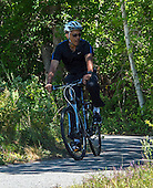 United States President Barack Obama, along with first lady Michelle Obama (not pictured) and daughter Malia Obama (not pictured), rides his bicycle on the Manuel F. Correllus State Forest bike path outside of West Tisbury, Massachusetts on Friday, August 15,  2014 during their summer vacation.<br /> Credit: Rick Friedman / Pool via CNP
