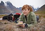A young teenage woman takes field notes while lying in the vegetation of Greenland's Tasermiut Fjord. The woman is a student that is part of the Cape Farewell Youth Expedition that was organized by the British Council of Canada.