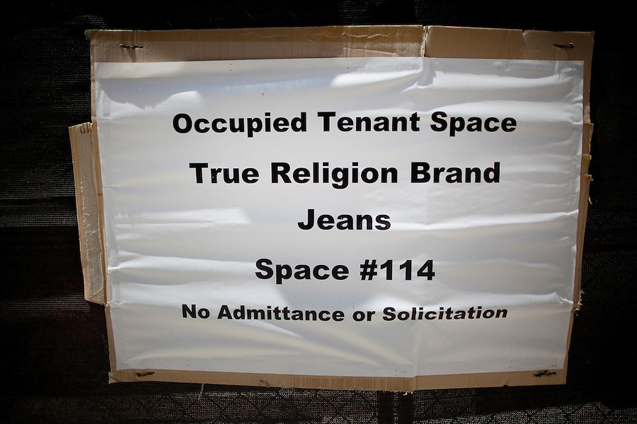 CREDIT: Daryl Peveto/LUCEO for The Wall Street Journal.SLUG: Macerich .ASSIGNMENT ID: 4429..Santa Monica, California, June 24, 2010 - A cardboard sign marks the location of high-end jean retailer True Religion at the Santa Monica Place mall which is slated to reopen in early August after receiving a $265 million makeover from its owner Macerich. Located at the end of Santa Monica's bustling Third Street Promenade and just two blocks from the Santa Monica Pier, the open-air mall is in the heart of Santa Monica's shopping district. The 2.5-year effort called for closing the dour, 28-year-old mall in early 2008, stripping it to its steel frame and remaking it as a modern shopping venue with several cutting-edge features. The three-level complex has no roof, reflecting the trend of recent years toward building open-air malls. Its first two levels are populated with a mix of fashion and luxury retailers including Tiffany & Co. and Juicy Couture sprinkled among big-box stores such as Nike and furniture-and-décor seller CB2. The mall will be anchored by Nordstrom and Bloomingdales. Retailers on its ground floor surround an expansive plaza. Santa Monica Place's bigger departure from the typical mall format is its third floor, which will be occupied entirely by restaurants. The collection is anchored by six high-end, chef-helmed eateries including the Ozumo sushi restaurant. Joining them are eight casual eateries and a gourmet market where shoppers can find groceries and meals to go. One of the restaurants' main selling points will be that their patio dining areas offer views of the Pacific..