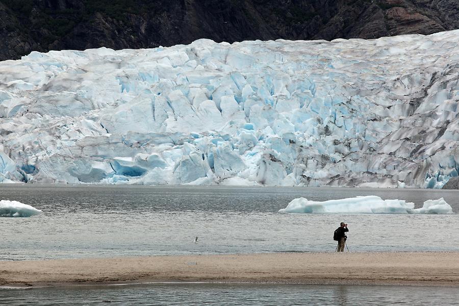 Photographer on sandbar at Mendenhall Lake photographing Mendenhall Glacier, Juneau, Alaska, USA