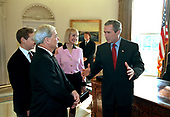 """United States President George W. Bush, right, speaks with Mr. and Mrs. Fal Oliver, Jr. and their son , Nathaniel, left, Wednesday, January 30, 2002 during a visit to the White House in Washington, DC by individuals who loaned art or played a role in the decoration of the Oval Office.. Oliver's grandfather, W.H. D. Koerner, painted """" A Charge to Keep"""" which  is hung in the Oval Office. <br /> Mandatory Credit: Paul Morse / White House via CNP"""