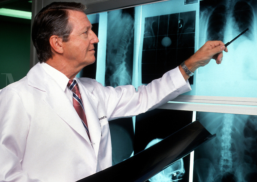 A mature male medical doctor examines an X ray.