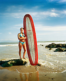 USA, California, portrait of smiling young woman standing with surfboard at the beach in Capitola