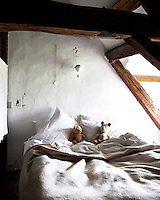 A small bedroom has been created in the eaves of this rustic cottage