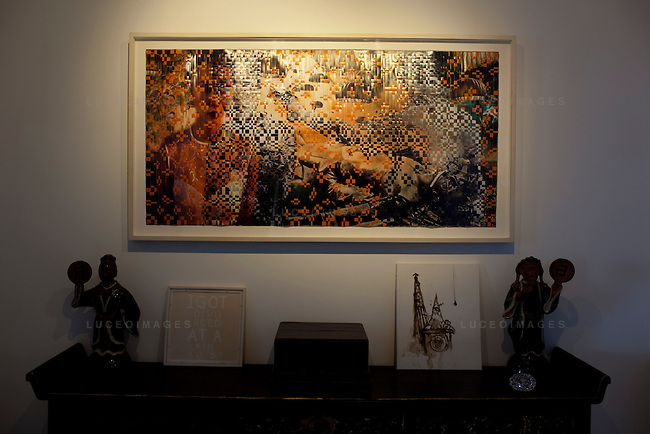 """An untitled piece from the series, """"From Vietnam to Hollywood"""" by Dinh Q. Le hangs in his Ho Chi Minh City home...Dinh Q. Le is a Vietnamese American fine arts photographer best known for his woven-photographs. Le uses traditional weaving techniques to combine mournful images from the Vietnam War with a sort of colorful fantasy. Le now works from his home in Ho Chi Minh City, Vietnam."""