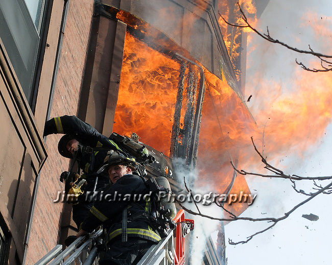 (Boston Ma 020114) Boston Firefighters from Ladder 15, wait for water as fire pours out of the 5th floor rear at 31 Massachusetts  Ave during the fire that went to seven alarms. (Jim Michaud  Photo) For Sunday