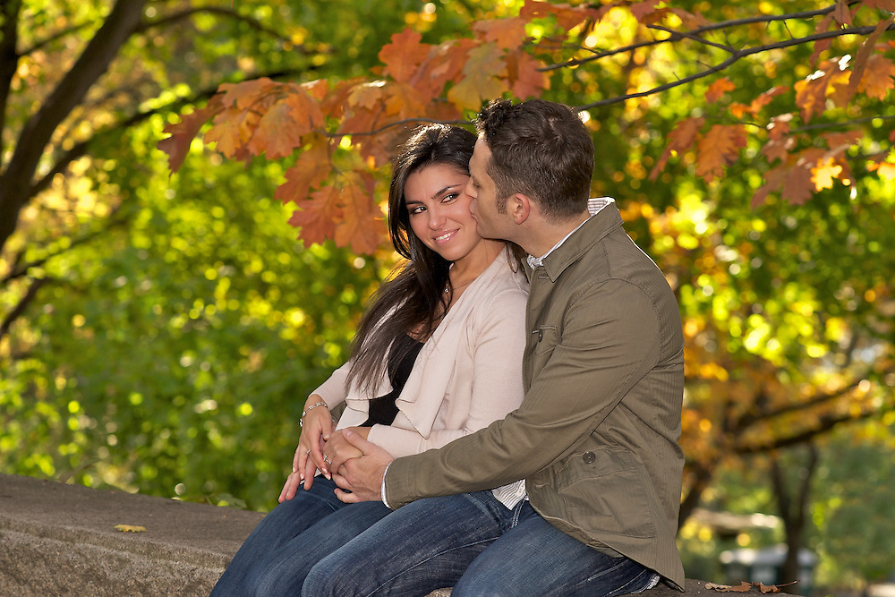 Engagement photo Riverside Park- couple sitting on stone wall with fall foliage in the background.