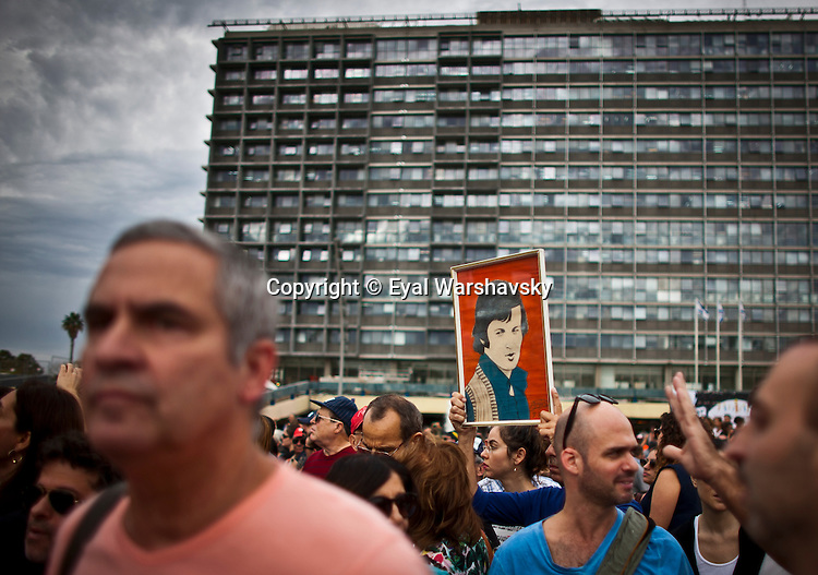 An Israeli man holds a photo of Singer Arik Einstein during his funeral in Tel Aviv  Wednesday Nov 27 2013. Thousands of Israelis flocked to Rabin Square in Tel Aviv on Wednesday to pay their last respects to legendary Israeli singer Arik Einstein, who died Tuesday night in Tel Aviv at the age of 75. photo by Eyal Warshavsky