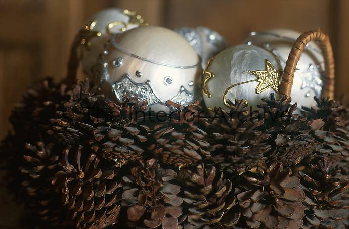 Close up of white pearly Christmas baubles in a basket made of pine cones