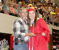 PHOTOS BY LYNN KUTTER ENTERPRISE-LEADER<br /> Morgan Williams, who served as a Farmington School Board member for 15 years, presents the diploma to his granddaughter, Kiera Peoples, at Farmington's 2019 commencement ceremony May 14 at Cardinal Arena.