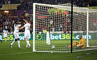 Pictured: Gylfi Sigurdsson of Swansea (2nd L) celebrating his goal with team mate Bafetimbi Gomis (L) while Everton goalkeeper Tim Howard sits on the ground dejected (R), making the score 2-0 to his team. Tuesday 23 September 2014<br />