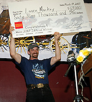 2007 Iditarod champion Lance Mackey hold up his $69,000 winner's check at the Nome awards banquet.