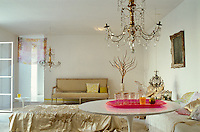 A pink plastic tray adds a touch of colour to the living room which is furnished with a combination of ancient and modern pieces