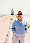 A young woman in sunglasses smiles while standing on a pier in front of a lighthouse