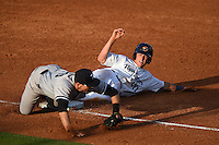 Lakeland Flying Tigers catcher Drew Longley (20) slides into third as third baseman Eric Jagielo (20) takes the throw during a game against the Tampa Yankees on April 5, 2014 at Joker Marchant Stadium in Lakeland, Florida.  Lakeland defeated Tampa 3-0.  (Mike Janes/Four Seam Images)