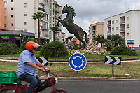 Spain. Balearic Islands. Minorca (Menorca). Ciutadella. An elderly man rides his moped on a traffic roundabout. He is wearing an orange helmet and drives by a bronze sculpture of a rising Menorquín horse. The Menorquín is a breed of horse indigenous to the island and is closely associated with the doma menorquina style of riding. The most valued quality of Menorquín horse is its suitability for the traditional festivals of Menorca. Horses and riders are usually at the centre of local fiesta celebrations. Riders pass through the crowds, executing caracoles and repeatedly performing the bot. The aim of the 'bot' is for the horse to stand on its hind legs while keeping its head and shoulders relaxed and without tension; the more often it is performed and the greater the distance travelled, the greater the applause of the crowd. The elevade, in which the horse beats the air with the front hooves, is also a part of the ritual of the fiesta. Ciutadella de Menorca or simply Ciutadella is a town and a municipality located in the western end of the island, which is part of the autonomous community of the Balearic. In Spain, an autonomous community is a first-level political and administrative division, created in accordance with the Spanish constitution of 1978, with the aim of guaranteeing limited autonomy of the nationalities and regions that make up Spain. 10.09.2019 © 2019 Didier Ruef