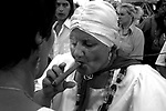 """An unidentified Mae, an Umbanda spiritual leader, smokes a cigar as she performs a """"santiguado"""", the cleaning of the aura of a person from negative energies. In order to satisfy the spirits """"incorporated"""" in the body they smoke cigarettes and drink alcohol. Photo by Quique Kierszenbaum"""