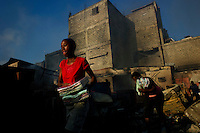 Port Au Prince, Haiti, Jan 25 2010.Everyday since the disaster, thousands of inpoverished inhabitants try to recover valuable goods in the ruins of downtown Port-au-Prince; sometimes it turns into downright looting of warehouse or shops; the police acts vigorously against the looters but it is sometimes difficult to draw the line between 'honnest' recovery and looting..