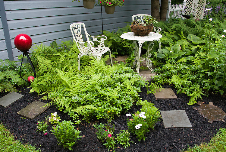 Shade garden with ferns, hostas, pachysandra, white wrought iron patio furniture, red gazing ball globe, blue house, mulch and stone pathway, hanging pots, planters containers, birdbath, turtle stepping stone