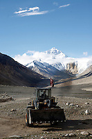 China started building a controversial 67-mile &quot;paved highway fenced with undulating guardrails&quot; to Mount Qomolangma, known in the west as Mount Everest, to help facilitate next year's Olympic Games torch relay./// A digger belches smoke as it clears the road in front of Rongbuk Monastery  on the road to Everest Base Camp.<br /> Tibet, China<br /> July, 2007