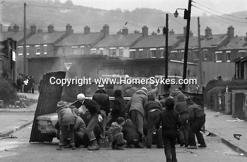 Ireland The Troubles. Belfast hijacked lorry set on fire by young IRA trouble makers and used as a barricade in petrol bomb fight against the British army seen in background. 1980s