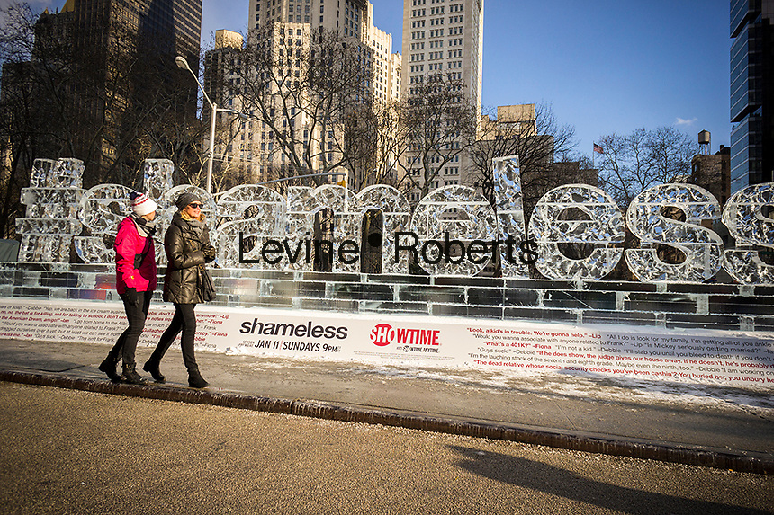 """Passer by amuse themselves with an ice sculpture promoting the Showtime series """"Shameless"""" is displayed in Madison Square in New York on Friday, January 9, 2015. The fifth season of the cable television show starts on Sunday.   (© Richard B. Levine)"""