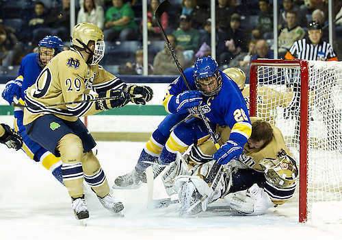 December 01, 2012:  Lake Superior State forward Domenic Monardo (#26) crashes into Notre Dame goaltender Mike Johnson (#32) during NCAA Hockey game action between the Notre Dame Fighting Irish and the Lake Superior State Lakers at Compton Family Ice Arena in South Bend, Indiana.  Notre Dame defeated Lake Superior State 6-1.