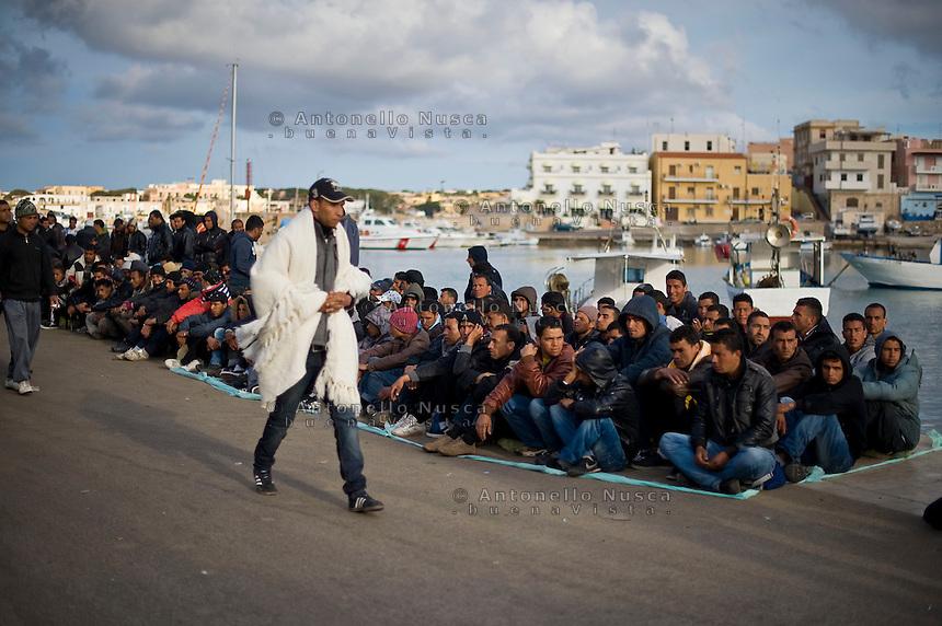 Immigrati Tunisini in attesa dell'identificazione prima di essere trasferiti nei centri di accoglienza. Illegal immigrants from Tunisia wait for transfer at the port of Lampedusa island, south Italy.