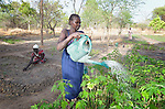 Deborah Ager Sawat waters plants and she and other women work in the fields at the Multi Agricultural Jesuit Institute of Sudan (MAJIS), an agricultural school located outside Rumbek, South Sudan.