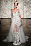 Model walks runway in a strapless dimensional sunflower lace sheath with train and removeable empire waist tulle overskirt, from Inbal Dror Fall 2018 bridal collection on October 5, 2017; during New York Bridal Fashion Week.