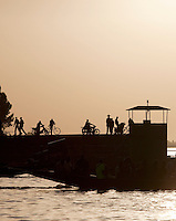 Silhouettes stand at the busy dock on the Niger River early in the morning, at Segou, Mali