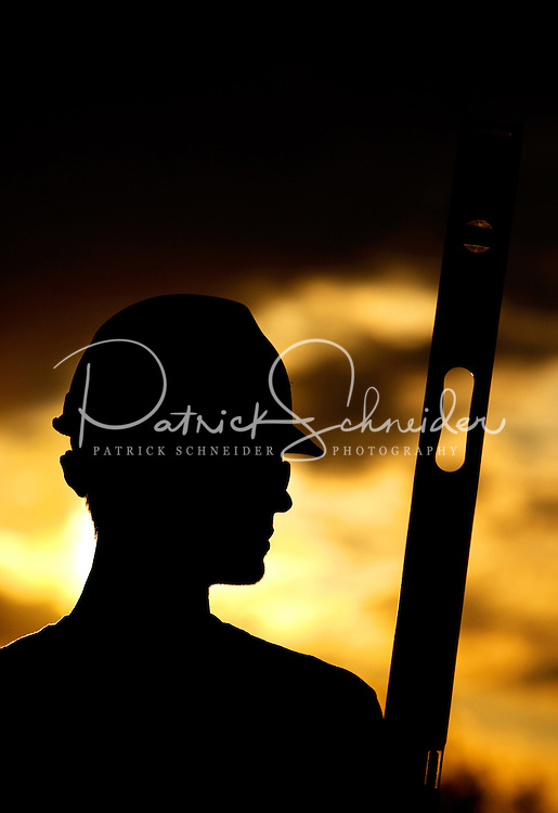 Silhouetted construction worker wearing hardhat and carrying level.