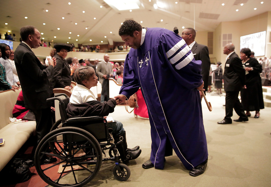 CHARLOTTE, NC - NOVEMBER 2:  The Rev. William Barber II,  president of the North Carolina NAACP, shakes hands with Ella Moore at St. Paul Baptist Church in Charlotte, NC, on Sunday, November 2, 2014.  Barber has been instrumental as an activist for voter rights.  (Photo by Ted Richardson/For The Washington Post)