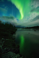 Northern lights reflect in river near Abiskojaure hut, Kungsleden trail, Lapland, Sweden