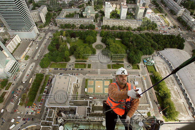 Overlooking the city, a maintainance man abseils down the side of the Soviet-built Palace of Culture after working on the antennae at the top of the building..