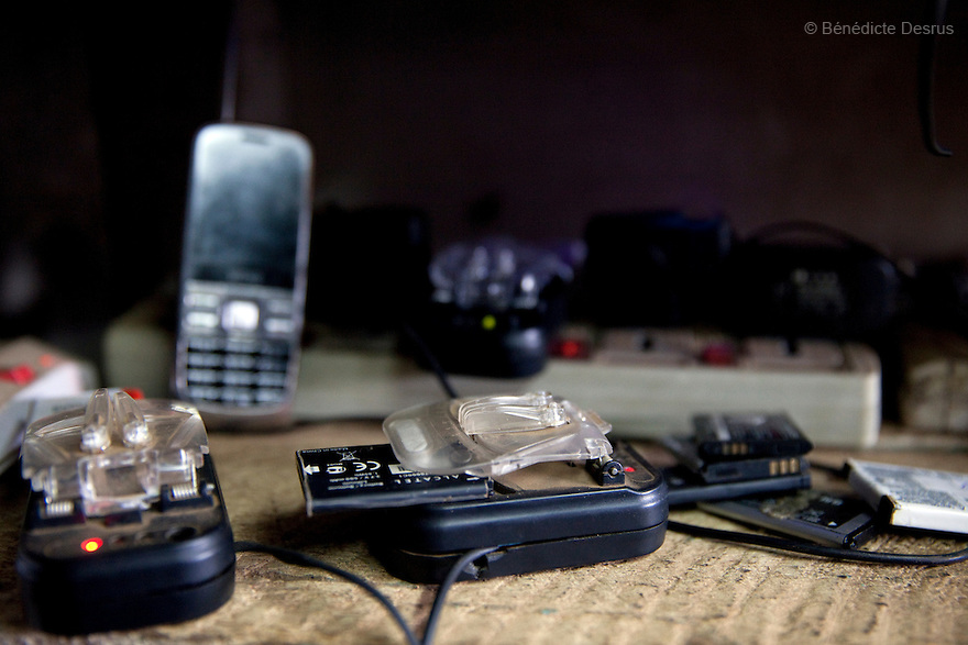 A Kenyan man is charging mobile phone battery at the price of  20 Kenyan Schillings (0.23 US dollar) at a shop in Nairobi slum on March 22, 2013. (Photo by Benedicte Desrus)