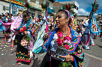 A dancer (danzante), holding flowers, performs in the religious parade within the Corpus Christi festival in Pujilí, Ecuador, 10 June 2012. Every year in June, thousands of people gather in a small town of Pujili, high in the Andes, to celebrate the Catholic feast of Corpus Christi. Introduced originally during the Spanish conquest of South America, this celebration merges Catholic rituals of Holy Communion with the traditional Andean harvest and sun festivities (Inti, the Inca sun god). Women dancers perform wearing brightly colored costumes while men dancers wear chest ornaments and heavy elaborate headdresses adorned with mirrors, jewelry, or natural items (shells). Being a dancer in the Corpus Christi ceremonial parade (El Danzante) is considered an honour and a privilege by the indigenous people in Ecuador.