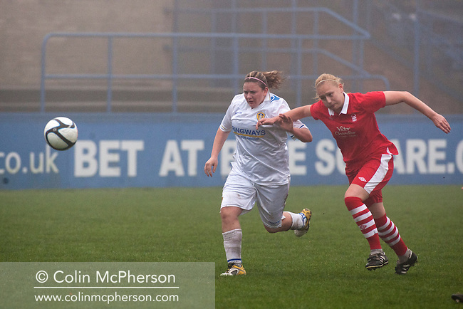 Leeds United Ladies FC striker Carey Huegett (left) chasing the ball, during the first half against Nottingham Forest Ladies FC in an FA Premier League National Division fixture at the Throstle Nest, Farsley, West Yorkshire. The match ended in a one-all draw, watched by fewer than 50 spectators at the club's regular home ground. Formed in 1989, Leeds United Ladies has been one of England's top women's sides for most of the last ten years and played in the top winter league for ladies' teams.