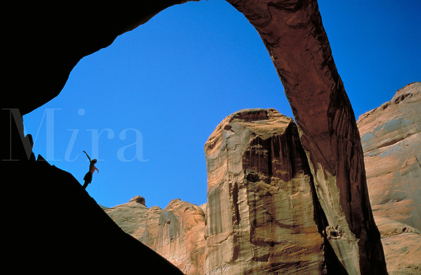 A hiker enjoys the view from beneath Rainbow Bridge, the world's largest natural arch along Lake Powell, Arizona. Hiker. Lake Powell Arizona USA.