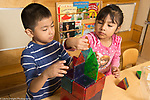Education Preschool 4 year olds boy and girl working together on building a structure from color plastic magnetic blocks