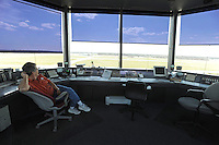 "Mick Moore mans the air traffic controller's tower at the Elkhart Municipal Airport in Elkhart, Indiana on April 8, 2009.  As part of the ""bail out"" funds, one of two runways will be repaired; airport manager Andy Jones said he had to turn down the request from Air Force One and the president's advance staff, citing the weight of the aircraft and the fragile state of the runways, to land at Elkhart Municipal Airport."