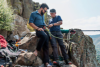 Owner of Rocky Mountain Slackline Dakota Collins (left), tightens the harness of Adventurist columnist, Clint Carter before an attempt of a highline walk at North Tale Mountain in Golden, Colorado, Tuesday, August 29, 2017. Carter take on a vertigo-inducing highline&nbsp;that stretches across a traverse after only 4 days of training.<br /> <br /> Photo by Matt Nager
