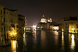 ITALY, Venice.  A view from Ponte dell' Accademia bridge of the Grand Canal at night. The domes of the Basilica di Santa Maria della Salute can be seen in the distance.