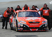 Sept. 20, 2008; Dover, DE, USA; Nascar Sprint Cup Series driver Tony Stewart is pushed to the garage by his crew during practice for the Camping World RV 400 at Dover International Speedway. Mandatory Credit: Mark J. Rebilas-