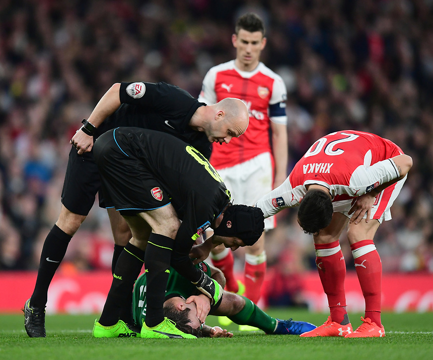 Arsenal's Petr Cech, left, Referee Anthony Taylor, centre, and Arsenal's Granit Xhaka check on Lincoln City's Matt Rhead who suffered a facial injury<br /> <br /> Photographer Chris Vaughan/CameraSport<br /> <br /> The Emirates FA Cup Quarter-Final - Arsenal v Lincoln City - Saturday 11th March 2017 - The Emirates - London<br />  <br /> World Copyright &copy; 2017 CameraSport. All rights reserved. 43 Linden Ave. Countesthorpe. Leicester. England. LE8 5PG - Tel: +44 (0) 116 277 4147 - admin@camerasport.com - www.camerasport.com