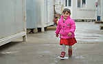 "A displaced girls walks among ""caravans,"" manufactured housing units for displaced families, in the village of Bakhtme, Iraq. The community was flooded with displaced families when the Islamic State group took over nearby portions of the Nineveh Plains in 2014. The community includes a ""child-friendly space"" sponsored by the Christian Aid Program Nohadra - Iraq (CAPNI), offering displaced children and children from the host community an opportunity to play and learn."