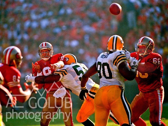 San Francisco 49ers vs. Green Bay Packers at Candlestick Park Saturday, January 6, 1996.  Packers beat 49ers  27-17.  Green Bay Packers linebacker Fred Strickland (55) hits San Francisco 49ers quarterback Steve Young (8) after he makes pass.