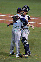 Pitcher Matt Wivinis (16) of the Charleston RiverDogs embraces catcher Eduardo Navas (11) after earning the save in Game 2 of the South Atlantic League Southern Division Playoff against the Greenville Drive on Friday, September 8, 2017, at Fluor Field at the West End in Greenville, South Carolina. Charleston won, 2-1, and the series is tied at one game each. (Tom Priddy/Four Seam Images)