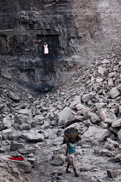 Children digging and carrying out coal from an open cast mine near Bokapahari village. Coal fires rage just below the surface of the ground, making it too hot to walk with naked feet. Noxious gases spew up from fissures, rendering the environment toxic. Residents who live above the furnace make $2 a day collecting small chunks of coal that they sell to illegal middlemen. One or two houses collapse annually into vast underground caverns left unfilled by abandoned mining operations.